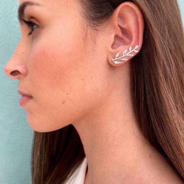 Pendientes trepadores con forma de ramita con hojas intercaladas por ambos lados, diseñado con curva que sigue la forma del lóbulo, quedando este perfectamente integrado en la oreja.