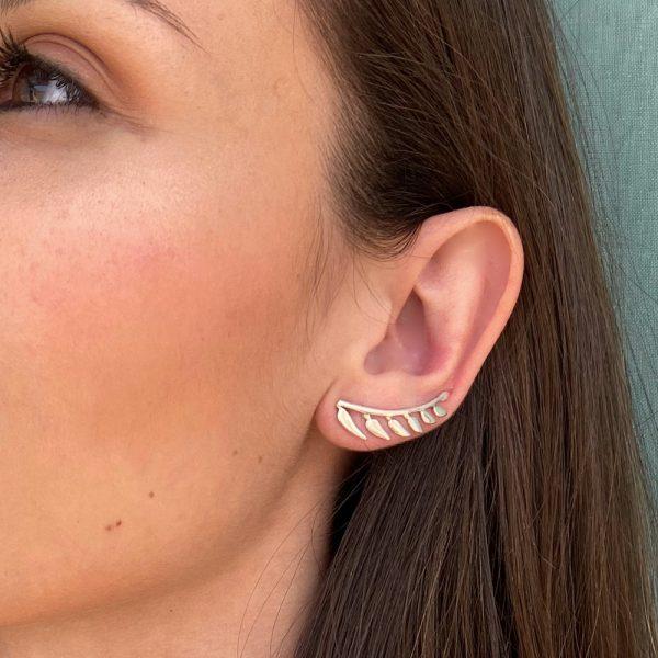 Pendientes de plata trepadores con forma de ramita de la que por un lado salen siete hojas, la ramita tiene forma curva para seguir la forma del lóbulo, quedando esta perfectamente integrada en la oreja.