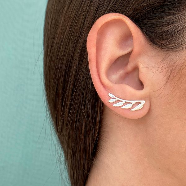 Pendientes trepadores con forma de ramita de la que por un lado salen cinco hojas, la ramita tiene forma curva para seguir la forma del lóbulo, quedando esta perfectamente integrada en la oreja.