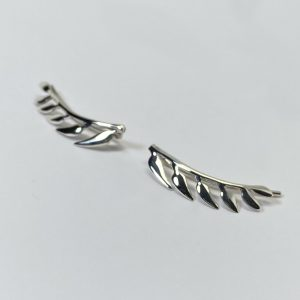 Pendientes trepadores con forma de ramita de la que por un lado salen seis hojas, la ramita tiene forma curva para seguir la forma del lóbulo, quedando esta perfectamente integrada en la oreja.